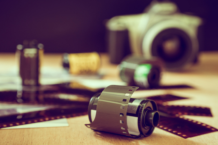 Roll of 35 mm photographic film with old camera on wooden table. Vintage tone