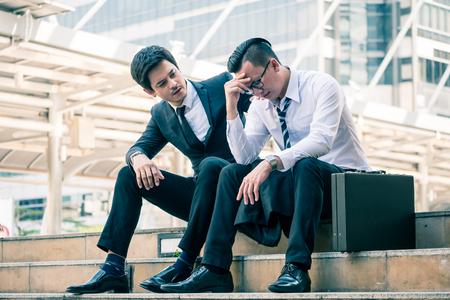 Frustrado joven empresario asiático sentado en la oficina al aire libre después de haber fallado en un nuevo proyecto, sus colegas intentaron tranquilizarlo. Foto de archivo