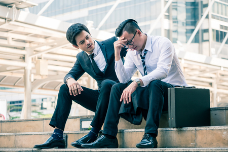Frustrated Asian young business man sitting outdoor office after he had failed in new project, his colleagues tried to reassure his. Stockfoto - 100743627