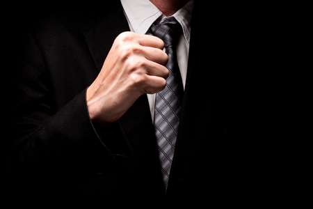 Close up of man in black suit with hand gesture on black background.