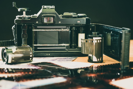 Roll of 35 mm photographic film with old camera on wooden table.