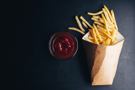 Top view of French fries with ketchup on black background. copy space Banco de Imagens