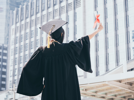 Graduation day, Back view of Asian woman with graduation cap and gown holding diploma, Successful concept Stock Photo