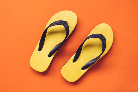 Top view of Yellow flipflop on orange background Stock Photo