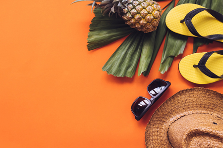 Top view of Summer accessories on orange background. copy space