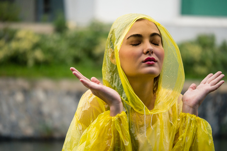 Young beautiful happy woman in yellow raincoat enjoying the rain