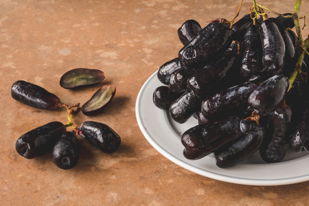 Black seedless moon drops grape or Witch fingers grape in white plate on brown grunge background 스톡 콘텐츠
