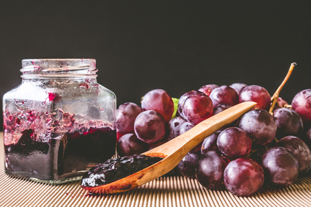Red grapes and jam on wooden table with black background Banco de Imagens