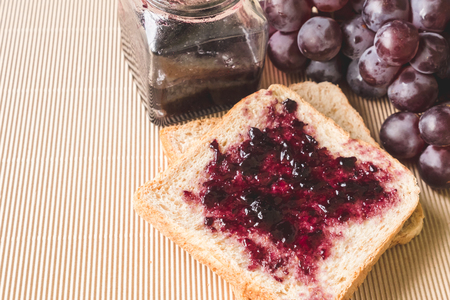 Whole wheat bread with grape jelly spread  on wooden table. copy space