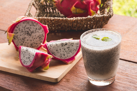 A glass of dragon fruit smoothie and fresh dragon fruit on wooden table