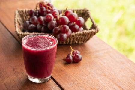 Glass of Grape juice smoothie on wooden table