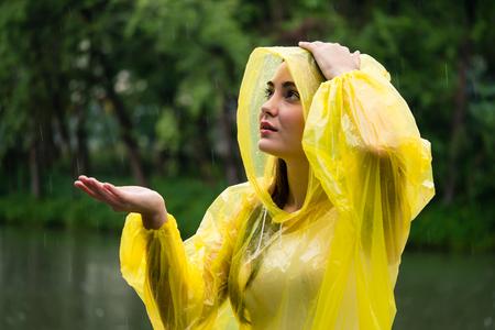 Junge schöne glückliche Frau im gelben Regenmantel, der den Regen genießt Standard-Bild