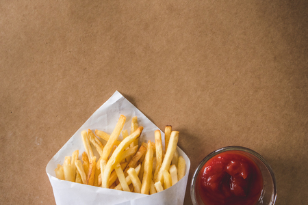 Top view of French fries with ketchup on wooden table. Copy space