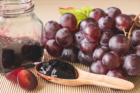 Red grapes and jam on wooden table