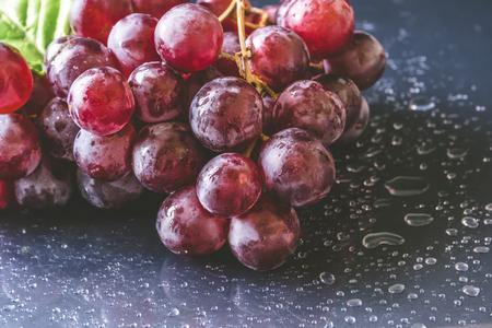 Cierre de uvas rojas con gotas de agua sobre fondo negro Foto de archivo - 102001800