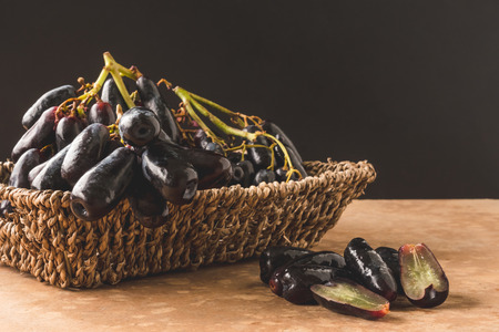 Black seedless moon drops grape or Witch fingers grape in basket with black background