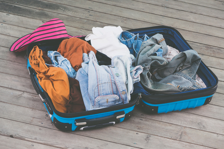 Open travelers bag with clothing, accessories on wooden floor.