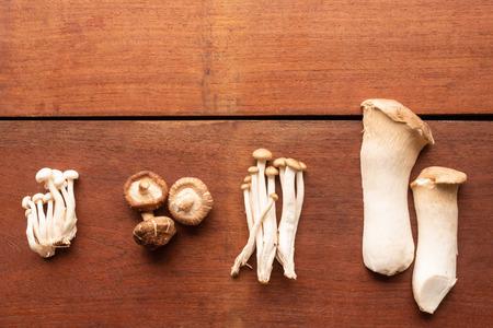 Mixed organic mushrooms on wooden table 스톡 콘텐츠