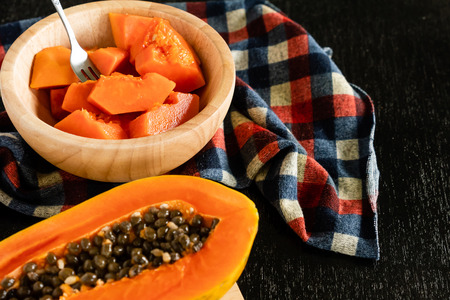 Slices of sweet papaya in wooden bowl on black table Stock Photo