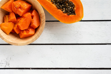 Slices of sweet papaya in wooden bowl on wooden table. copy space
