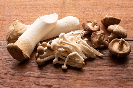 Mixed organic mushrooms on wooden table Banco de Imagens