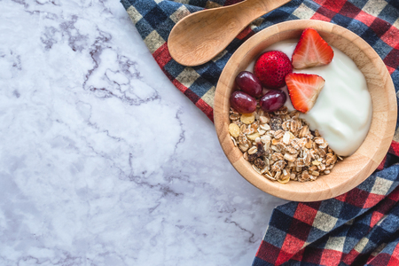 Healthy breakfast. Bowl of homemade muesli with yogurt and fresh fruits on marble table. copy space
