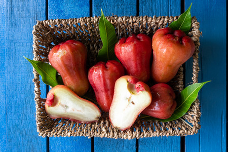 Top view of rose apples in basket on blue wooden table Imagens