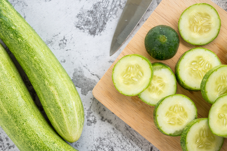 Fresh cucumber slices on a cutting board. Top view