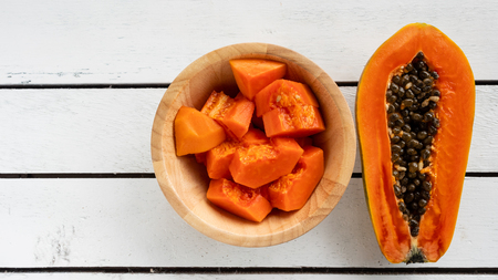 Slices of sweet papaya in wooden bowl on wooden table. Stock Photo