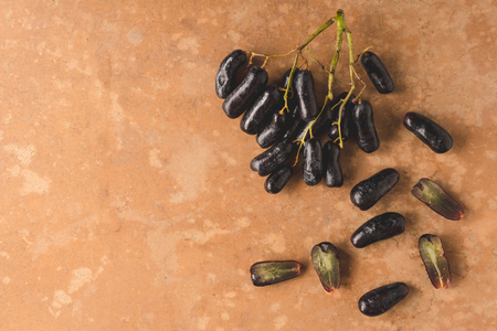 Black seedless moon drops grape or Witch fingers grape on brown grunge background. copy space Stock Photo