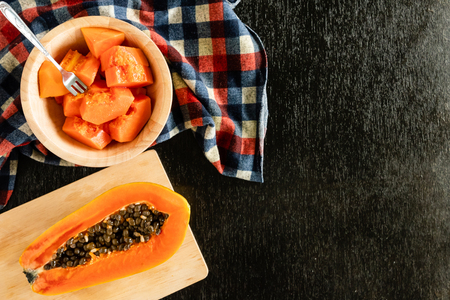 Slices of sweet papaya in wooden bowl on black table. copy space