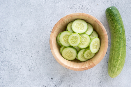 Fresh cucumber slices on a wooden bowl. Top view
