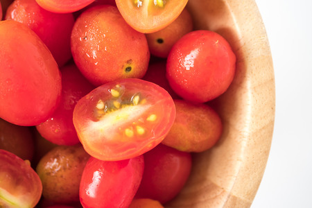 Close up of Plum tomatoes in wooden bowl on white background