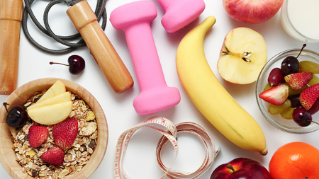 Top view of Oatmeal flakes, milk, fresh fruits and fitness equipments on white background. Imagens