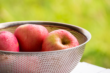 Close up of red apples in basket with natural green background