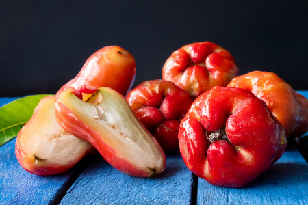 Close up of Rose apples on blue wooden table with black background Imagens