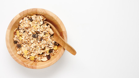 Top view of oatmeal flakes in wooden bowl on white background. copy space Stock fotó