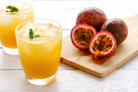 A glass of juice and fresh passion fruit on wooden table Reklamní fotografie