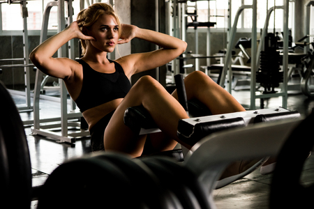 Attractive young woman doing sit up exercise with machine at the gym. Foto de archivo