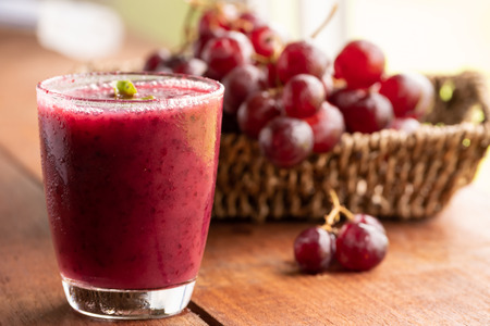Glass of Grape juice smoothie on wooden table Stock Photo