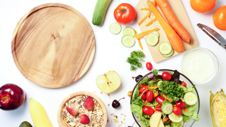 Top view of empty wooden plate, mixed vegetables salad, muesli and fresh fruits on white background.