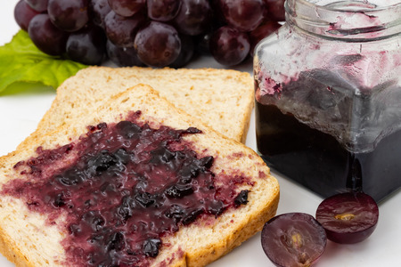 Whole wheat bread with grape jelly spread on a white background. Stockfoto