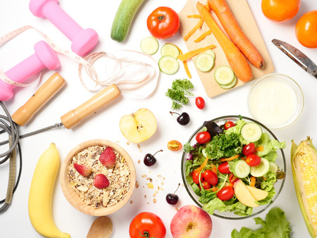Top view of mixed vegetables salad, muesli, fresh fruits and fitness equipments on white background.
