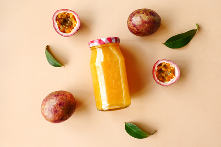A bottle of juice and fresh passion fruit on color background. Top view