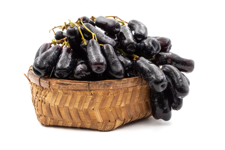 Black seedless moon drops grape or Witch fingers grape in basket on white background Stock Photo