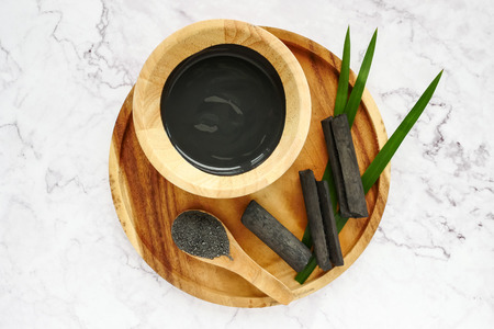 Facial mask and scrub by activated charcoal powder on marble table Stockfoto