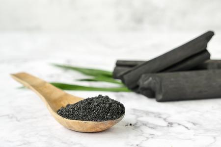 Węgiel aktywowany w proszku na marmurowym stole.
