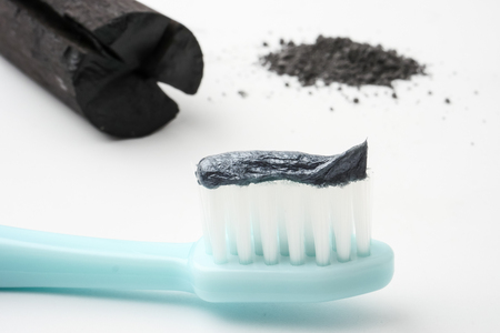 Toothpaste by activated charcoal powder on white background Stockfoto