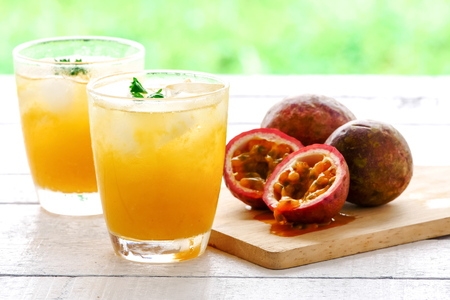 A glass of juice and fresh passion fruit on wooden table Stockfoto