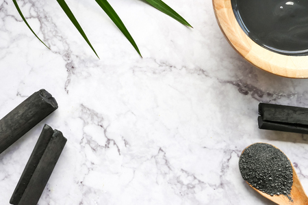 Facial mask and scrub by activated charcoal powder on marble table. Free space for text
